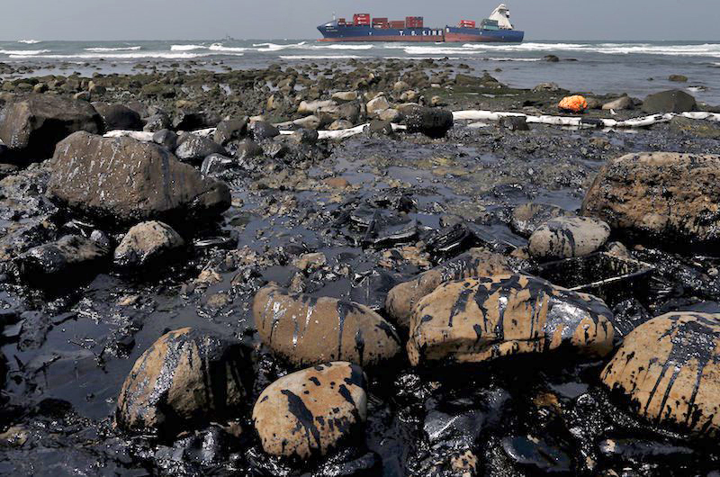 Rocks covered with oil that leaked from a cargo ship (background) owned by TS Lines Co are seen off the shores of New Taipei City, Taiwan, March 26, 2016. The oil spilled from the ship has contaminated 2 kilometer (1.24 miles) of water, according to local media. REUTERS/Tyrone Siu